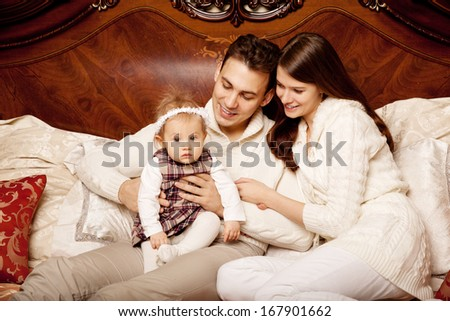 Young family in the bedroom. Mother, father and daughter in the interior. Mom, dad and baby are playing together.  - stock photo