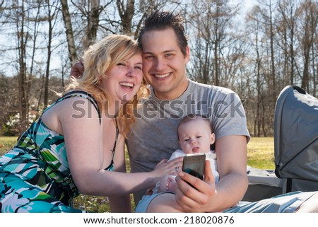 Young family is taking a selfie picture with their smartphone - stock photo