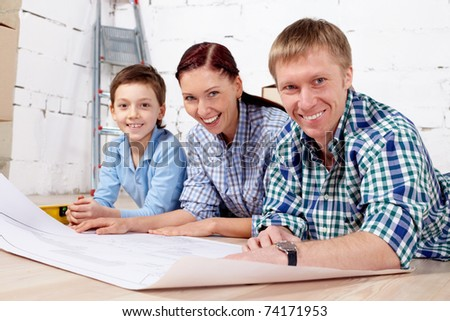 Young family looking at camera in new apartment
