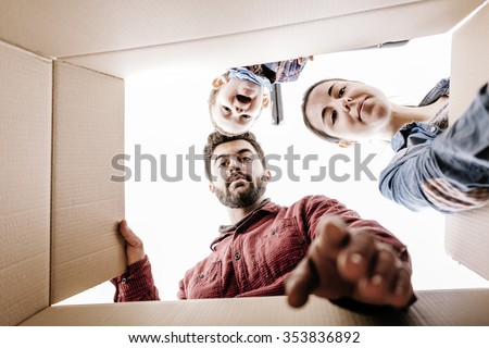 Young family looking in a box - stock photo