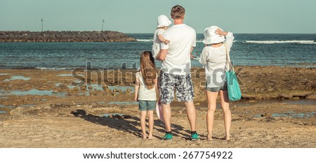 Young family of four members in the summer on the beach - stock photo
