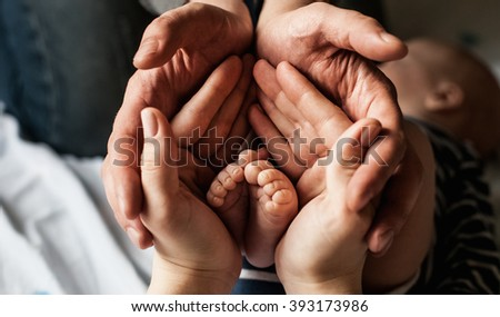 young family of mother of the father and kid. Mother and the father hold legs of the newborn child in the palms.