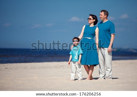 Young family of three having fun tropical beach