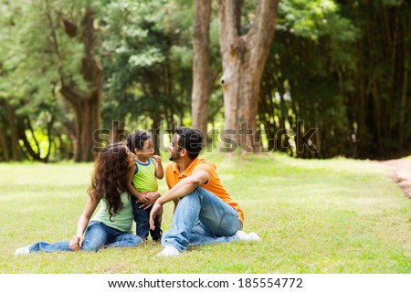 young family of three sitting together outdoors - stock photo