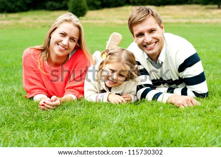 Young family of three spending a happy day outdoors. Relaxing on lush green grass - stock photo