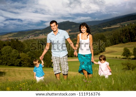 young family on the meadow at sunny day