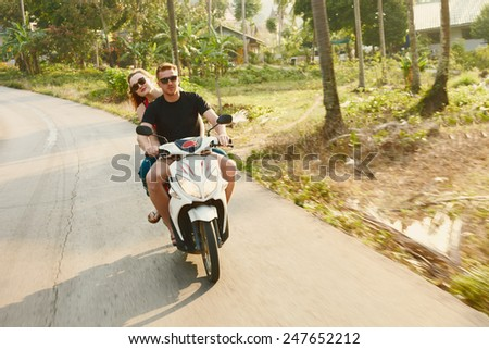Young family on the motorcicle on the asia travel road in morning sunlight - stock photo