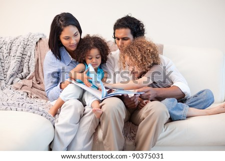 Young family on the sofa looking at the photo album together