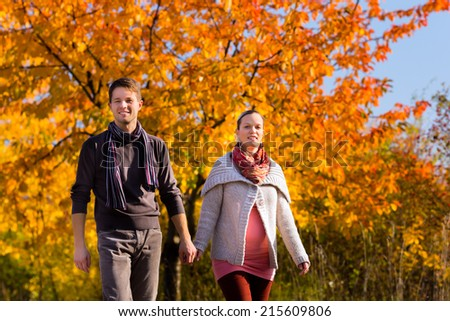 Young family or couple or man and pregnant woman walking through colorful trees in fall or autumn - stock photo