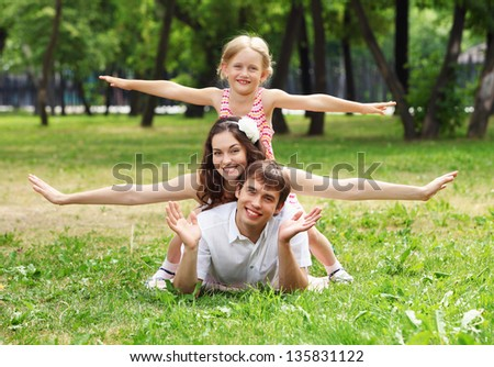 Young Family Outdoors on the grass in Park in summer - stock photo