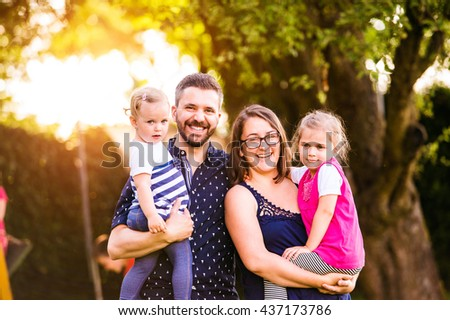 Young family outside in sunny summer park, green nature - stock photo