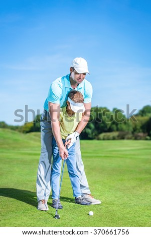 Young family playing golf - stock photo