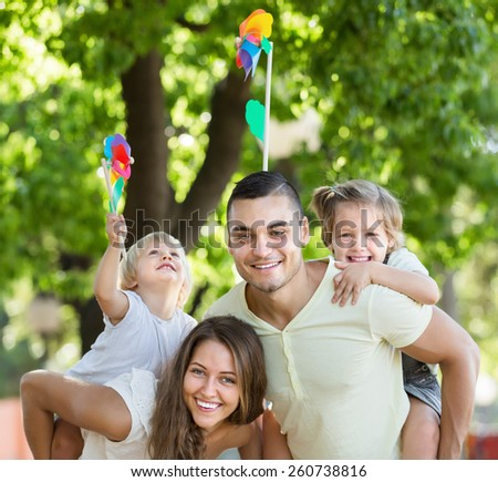 Young family playing windmills with children in park  - stock photo