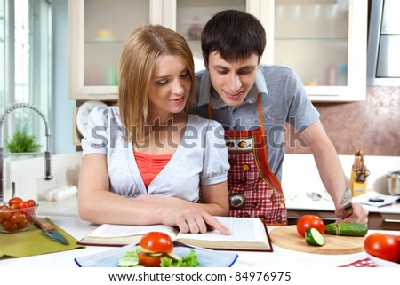 young family prepares a light salad - stock photo