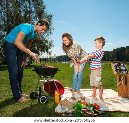 Young family preparing sausages on a grill outdoors  - stock photo