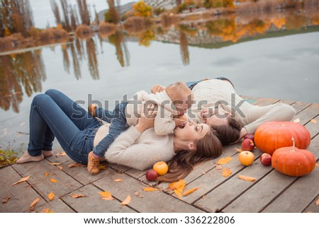 Young family resting on the lake shore