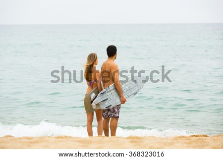 Young family resting on the shore with surf boards - stock photo