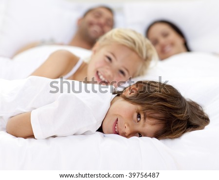 Young family resting together in parent's bed