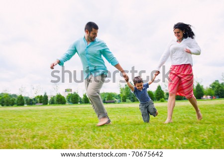 Young family running happy outdoors - stock photo
