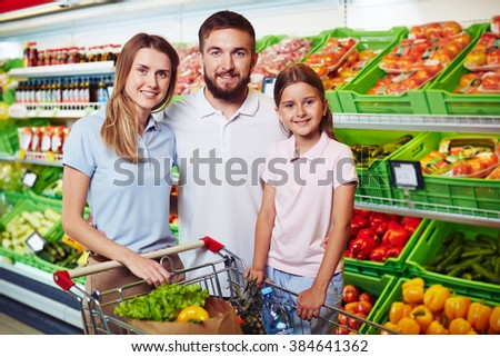 Young family shopping for vegetables in grocery shop - stock photo