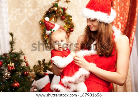 Young family sitting around the Christmas tree. Mom and baby in the New Year  interior.