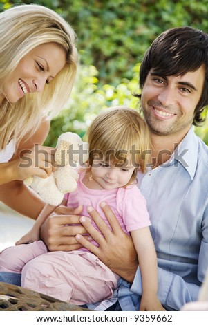 young family sitting in the garden in the summer time - stock photo