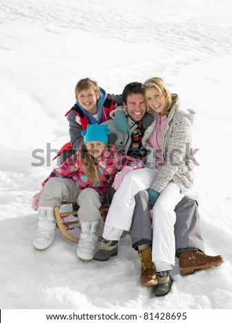 Young Family Sitting On A Sled In The Snow - stock photo
