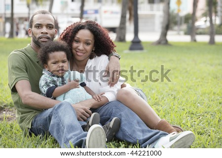 Young family sitting on the grass in the park - stock photo