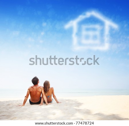 Young family sitting on warm sand by a sea and looking to a blue sky with house shaped clouds - stock photo