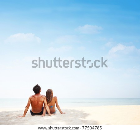 Young family sitting on warm sand by a sea and looking to somewhere