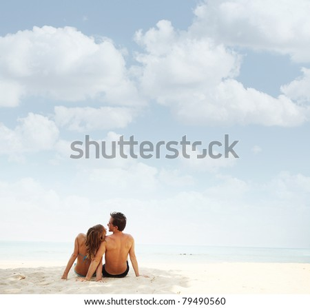 Young family sitting on white sand by sea and enjoying each other - stock photo