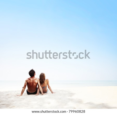 Young family sitting on white sand by sea and enjoying each other