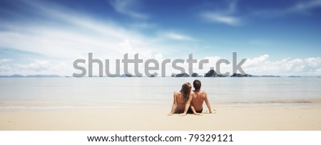 Young family sitting on white sand by sea and looking to the horizon - stock photo