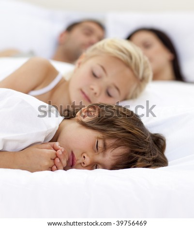 Young family sleeping together in parent's bed - stock photo