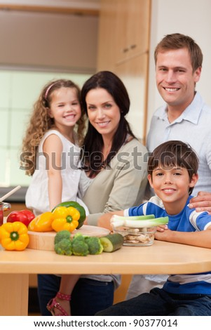 Young family standing in the kitchen together