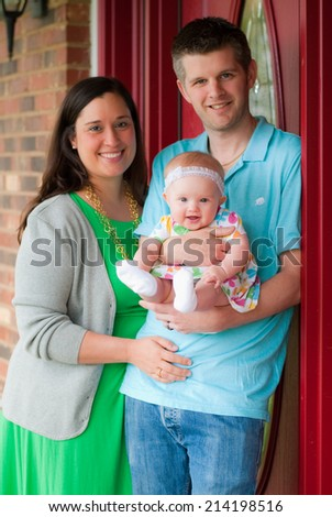 Young Family Standing Outside on the Porch - stock photo