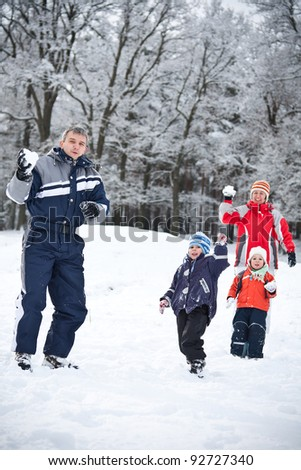 Young family throwing snowballs on winter vacation - stock photo