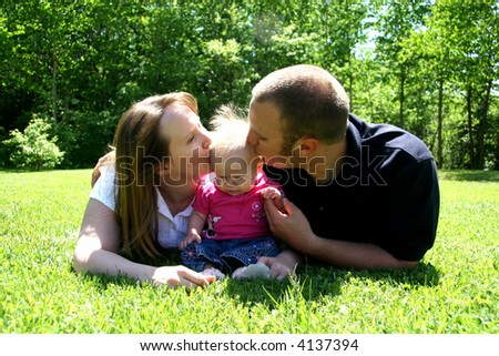 Young family together, kissing baby - stock photo