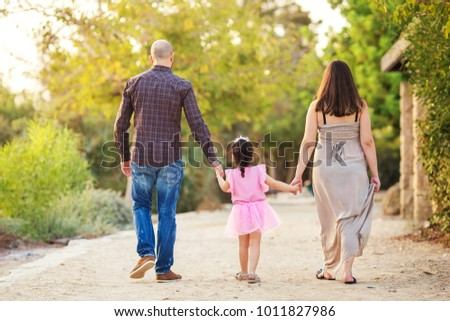 Young family walking in park and holding hands