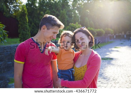 Young family walking in the Park and the boy shows parents direction. - stock photo