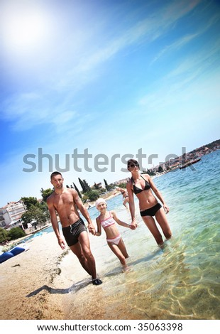 Young family walking on a beach - stock photo