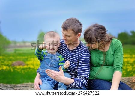 Young family walking on the meadow with yellow flowers in spring.