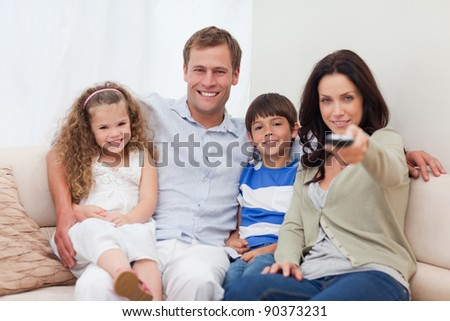 Young family watching television - stock photo