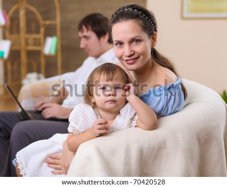 young family with a daughter at home in the living-room