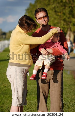 Young family with adorable young child outdoor in autumn - stock photo