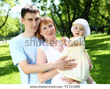 Young family with baby daughter together in the park - stock photo