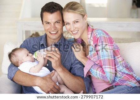Young Family With Baby Feeding On Sofa At Home - stock photo