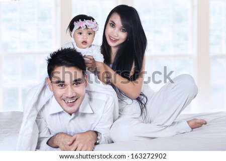 Young family with baby girl playing on the bed at home - stock photo