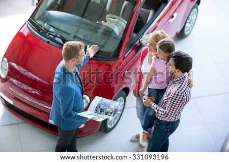 Young family with car agent in  the car dealership  saloon - stock photo