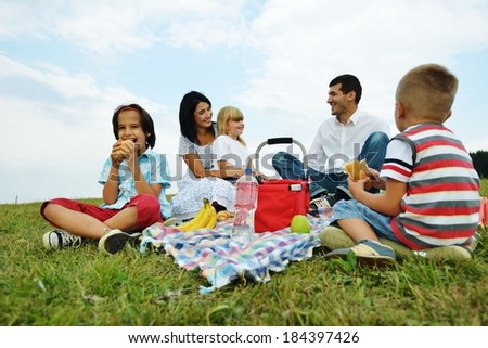 Young family with kids having picnic on green grass meadow in nature - stock photo